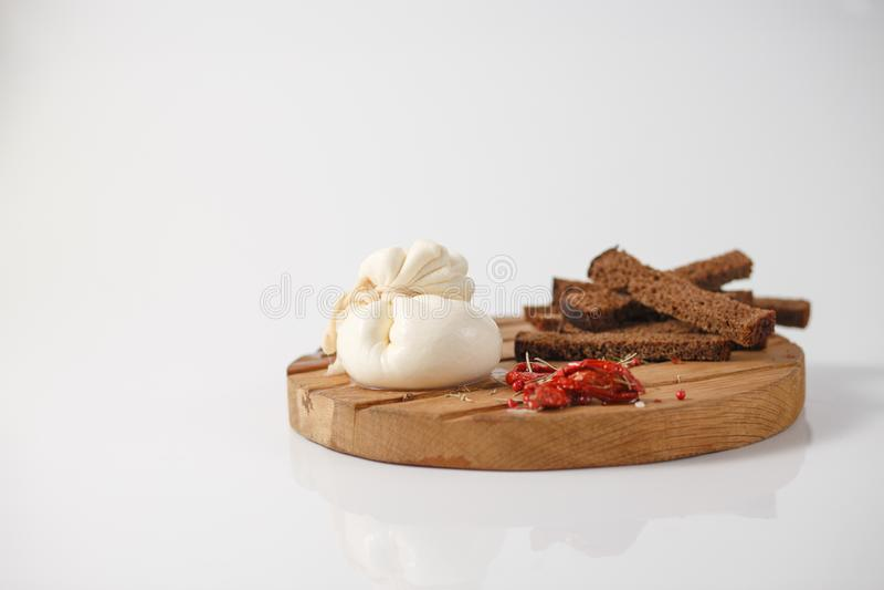 Le fromage de Burrata sur le conseil en bois avec des épices, et des biscuits de seigle photographie stock