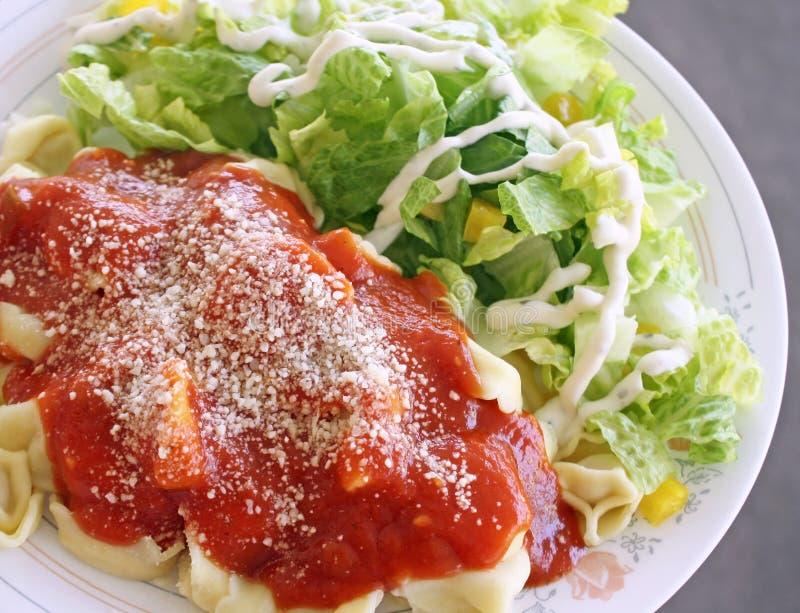 Le fromage a rempli ravioli de sauce tomate faite maison complétée avec le parmesan râpé Salade avec le habillage crémeux du côté images stock