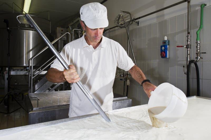 Le fromager verse la présure photographie stock