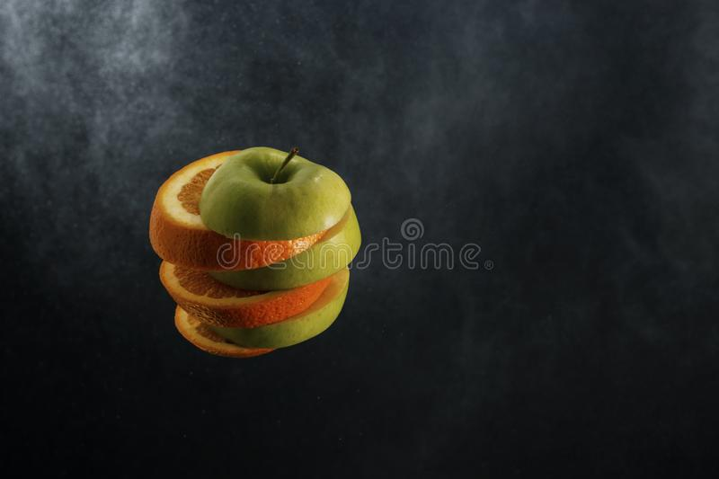 Le fruit orange juteux orange et la coupe verte de pomme en plusieurs tranches ont empilé ensemble sur un fond foncé de gradien photographie stock libre de droits