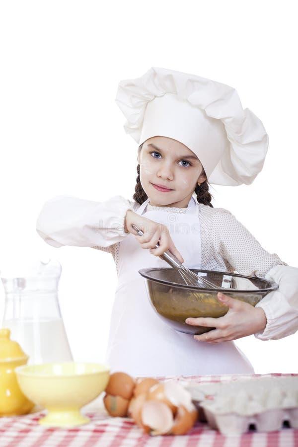 Le fruste del cuoco della bambina sbattono le uova in un grande piatto fotografia stock libera da diritti