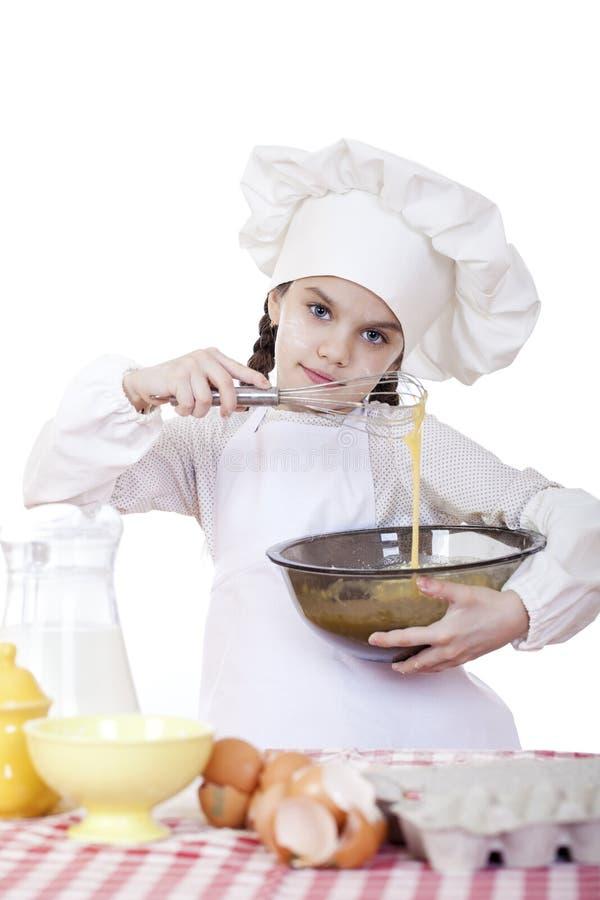 Le fruste del cuoco della bambina sbattono le uova in un grande piatto fotografie stock