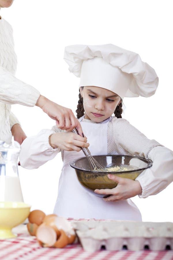 Le fruste del cuoco della bambina sbattono le uova in un grande piatto immagine stock