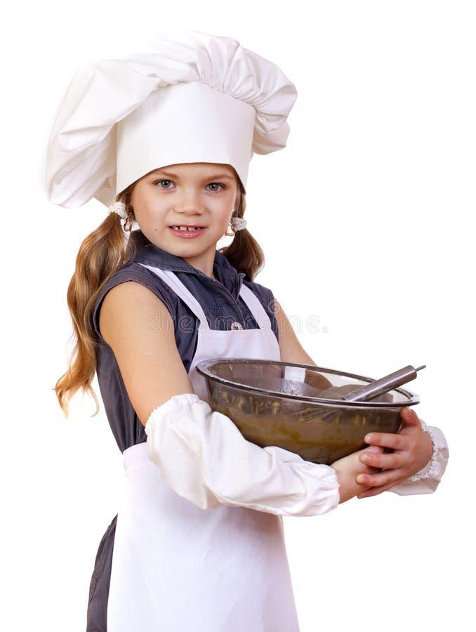 Le fruste del cuoco della bambina sbattono le uova in un grande piatto fotografie stock libere da diritti