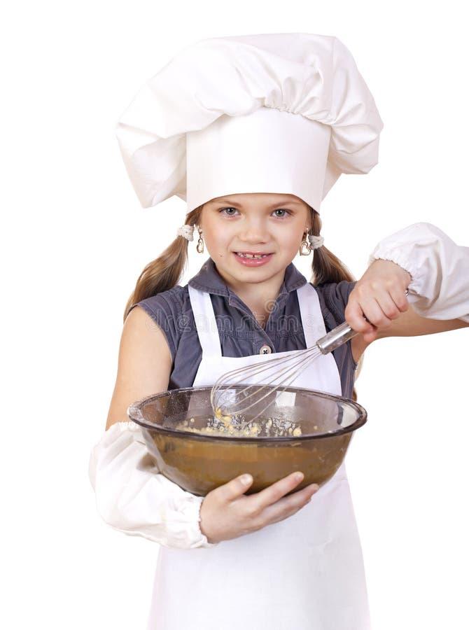 Le fruste del cuoco della bambina sbattono le uova in un grande piatto immagini stock libere da diritti