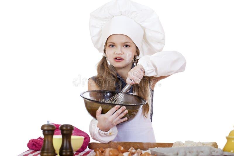 Le fruste del cuoco della bambina sbattono le uova in un grande piatto fotografia stock