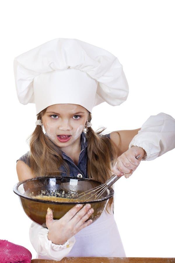 Le fruste del cuoco della bambina sbattono le uova in un grande piatto immagini stock