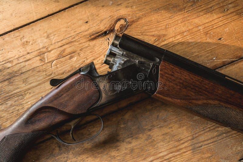 Le fusil de chasse a chargé des balles et des balles disponibles sur le plancher en bois, photographie stock