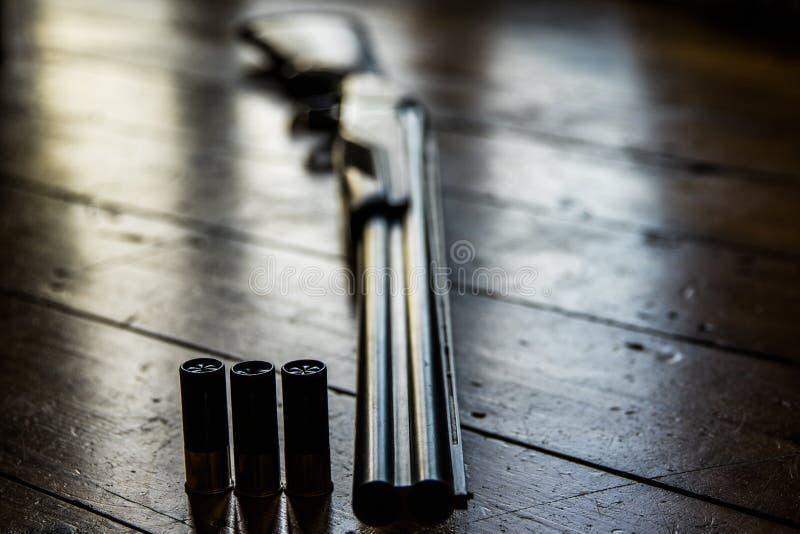 Le fusil de chasse a chargé des balles et des balles disponibles sur le plancher en bois, images stock