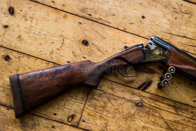 Le fusil de chasse a chargé des balles et des balles disponibles sur le plancher en bois, photos stock