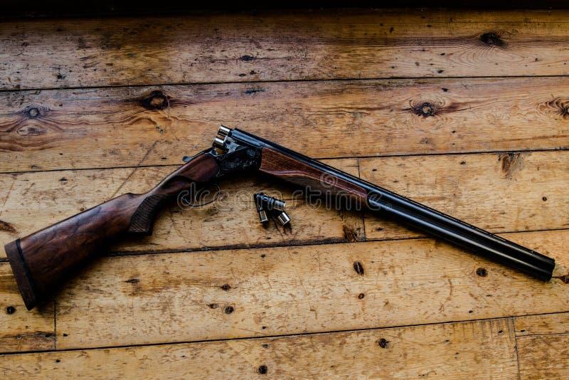 Le fusil de chasse a chargé des balles et des balles disponibles sur le plancher en bois, images libres de droits