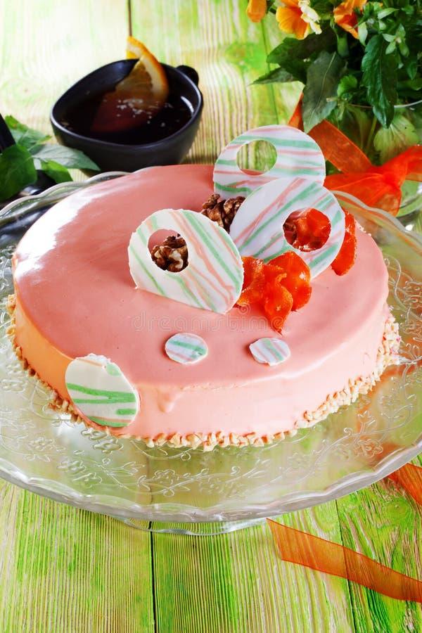 Le gâteau à la carotte en glaçage rose décoré avec les décorations en bois de table de chocolat de planche blanche de la vie séch photographie stock