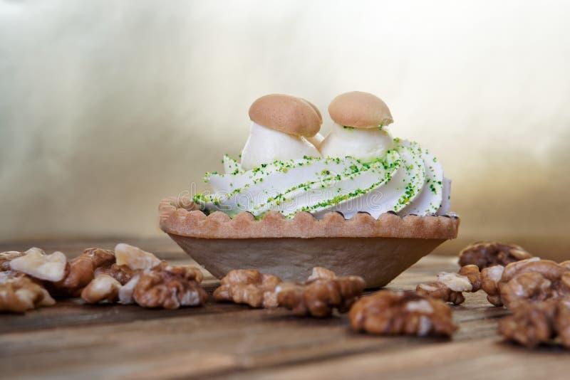 Le gâteau avec de la crème, semblable aux paniers avec des champignons, et les noix épluchées se trouvent sur une table en bois f images libres de droits