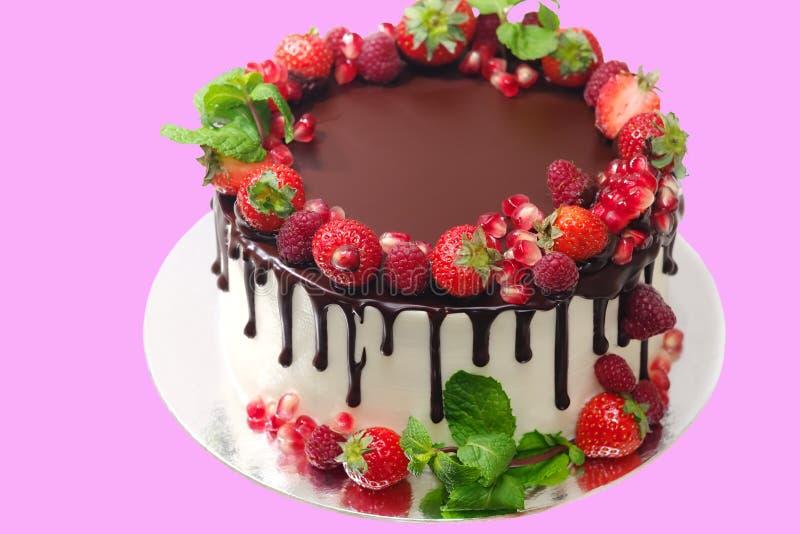 Le gâteau couvert de baies des feuilles en bon état de grenade de fraise de framboise a trempé avec du chocolat sur un fond blanc photographie stock libre de droits