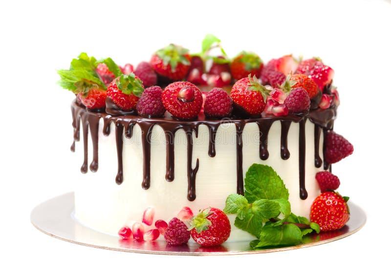 Le gâteau couvert de baies des feuilles en bon état de grenade de fraise de framboise a trempé avec du chocolat sur un fond blanc images libres de droits