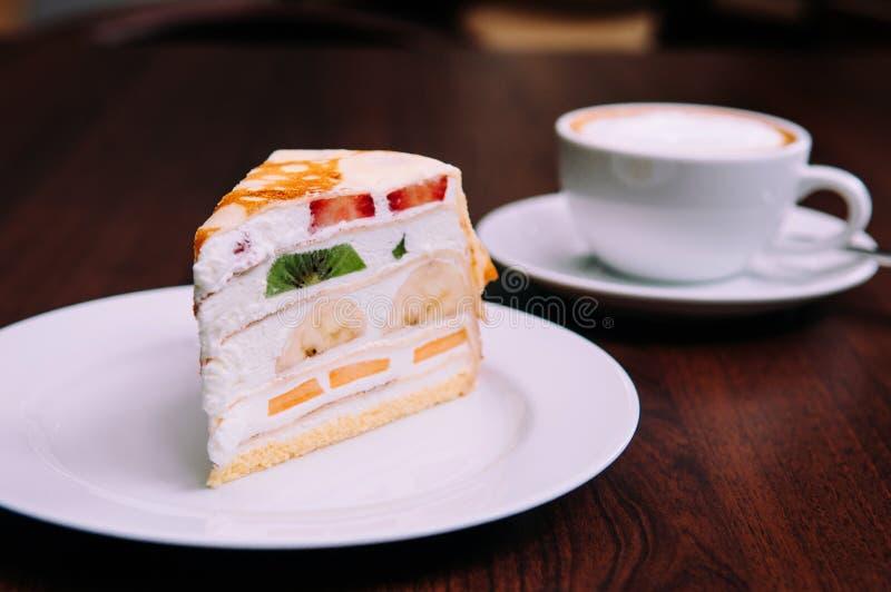 Le gâteau crémeux de crêpe avec le mélange porte des fruits sur le plat blanc en café de bekery photo libre de droits
