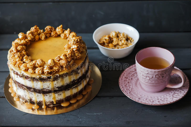 Le gâteau délicieux avec le maïs éclaté de caramel et le caramel sauce photographie stock