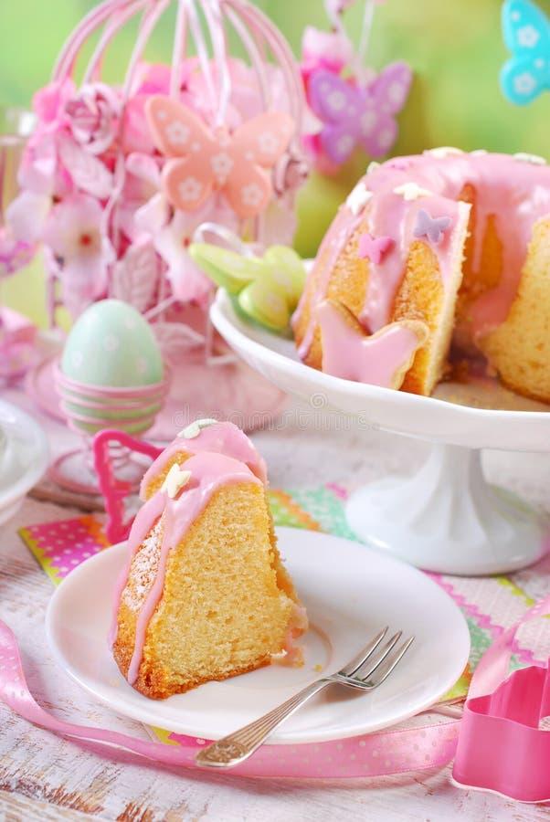 Le gâteau d'anneau de Pâques avec le glaçage et le papillon roses a formé le spri de sucre image libre de droits