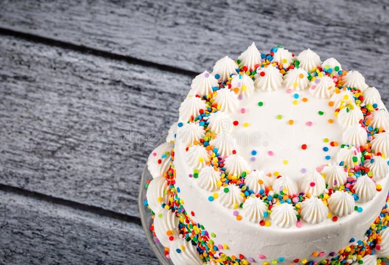 Le gâteau d'anniversaire avec coloré arrose image stock