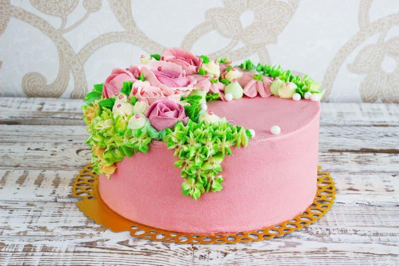Le gâteau d'anniversaire avec des fleurs s'est levé sur le fond blanc image libre de droits