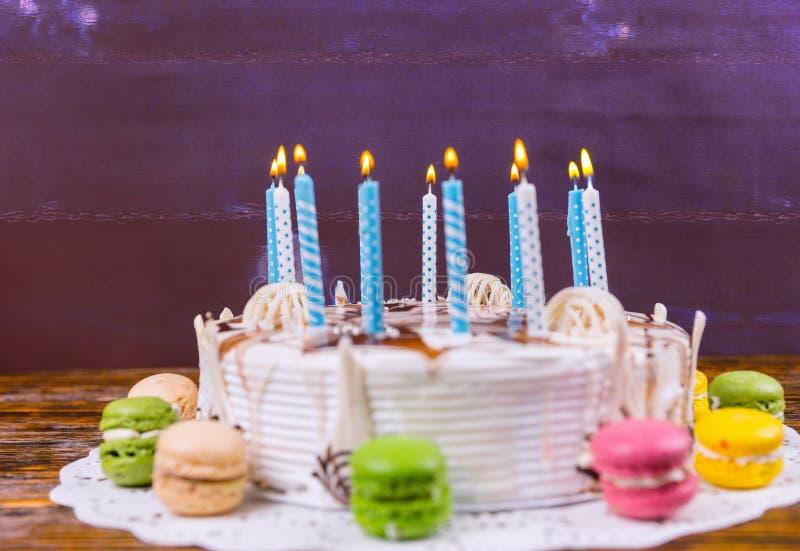 Le gâteau d'anniversaire avec un bon nombre de bougies brûlantes s'approchent du colore différent photo stock