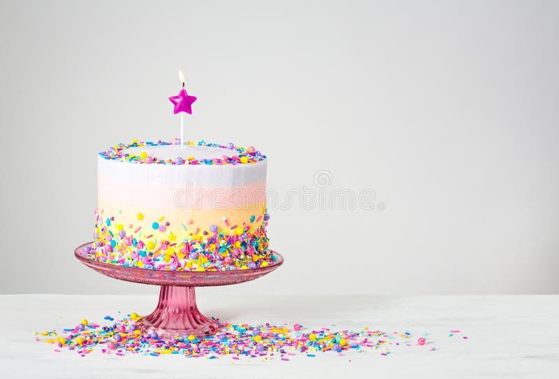 Le gâteau d'anniversaire coloré avec arrose photos stock