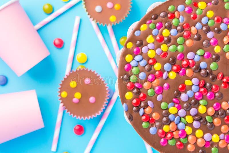 Le gâteau d'anniversaire de chocolat au lait avec la sucrerie vitrée multicolore arrose les pailles barrées de papier roses de ta photo libre de droits