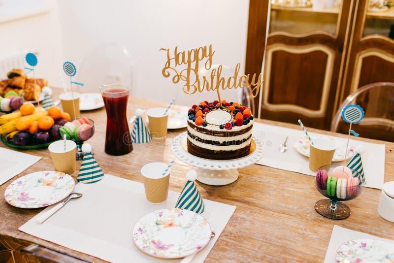 Le gâteau d'anniversaire servi par table d'esprit de vacances, ajournent complètement du fruit, de la compote, des plats vides et photo libre de droits