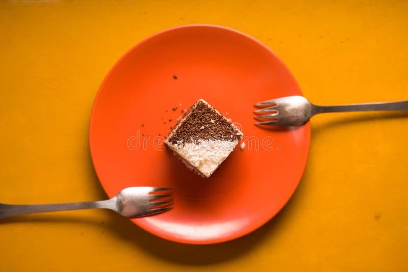 Le gâteau de chocolat avec la noix de coco ébrèche d'un plat en céramique image stock