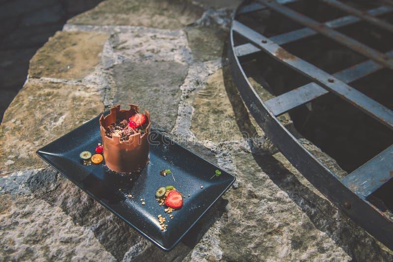 Le gâteau de chocolat exclusif comme la tour avec des fruits a servi du plat noir, photographie de produit pour la pâtisserie, de photographie stock libre de droits