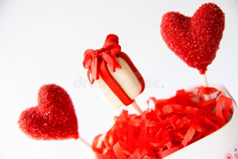 Le gâteau de coeur et de boîte-cadeau saute dans la tasse sur le fond blanc Jour de Valentine images libres de droits