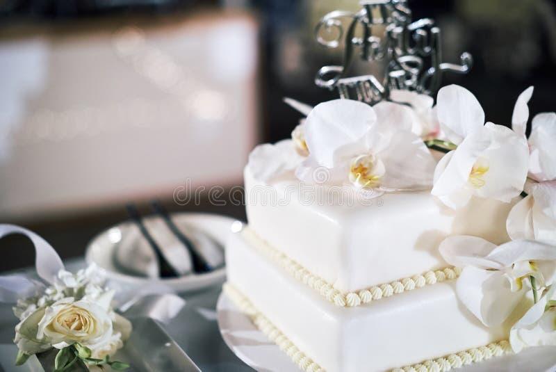 Le gâteau de mariage blanc, 2 couches, décorées des orchidées blanches - vue supérieure, fermée  image libre de droits