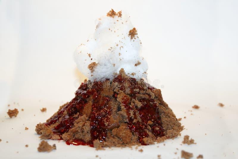 Le gâteau de volcan avec de la lave rouge de sauce à baie et la sucrerie floss images libres de droits