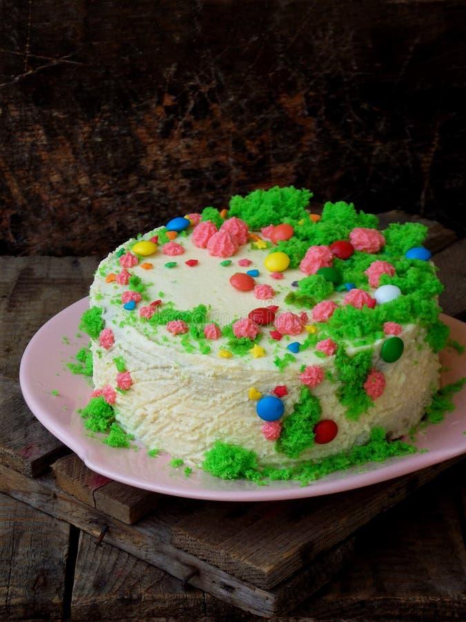 Le gâteau fait maison de pavot avec le biscuit d'écrou et la crème de crème anglaise a décoré la sucrerie de bonbons sur le fond  photo libre de droits