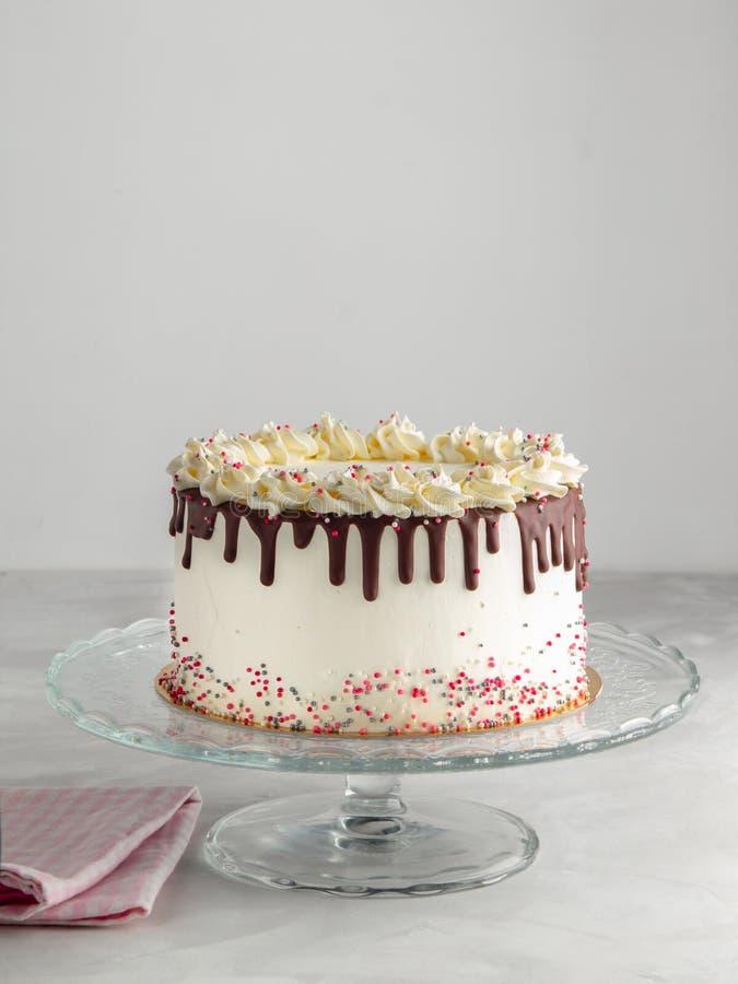Le gâteau posé d'égouttement d'anniversaire avec le ganache de chocolat et arrose sur un fond blanc avec le décor de partie horiz photos stock