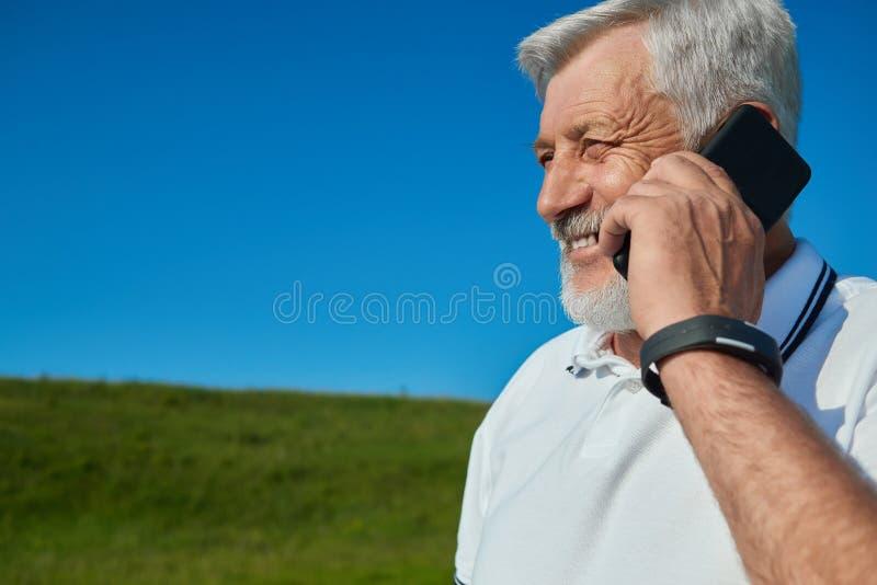 Le gamala mannen som talar på mobiltelefonen i fältet arkivbild