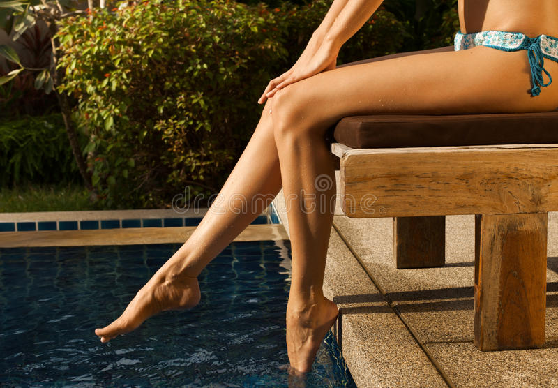 Gambe della bellezza della ragazza nello stagno immagine stock