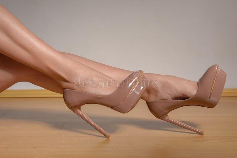 Le gambe ben fatto della donna che indossano il marrone hanno laccato le scarpe del tacco alto immagine stock