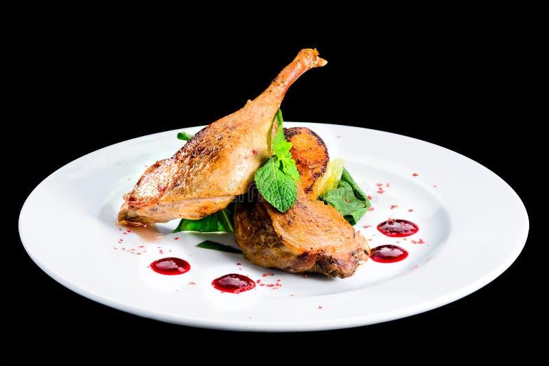 Le gambe cucinate deliziose succose dell'anatra sono servito con le erbe e la salsa dentro fotografia stock