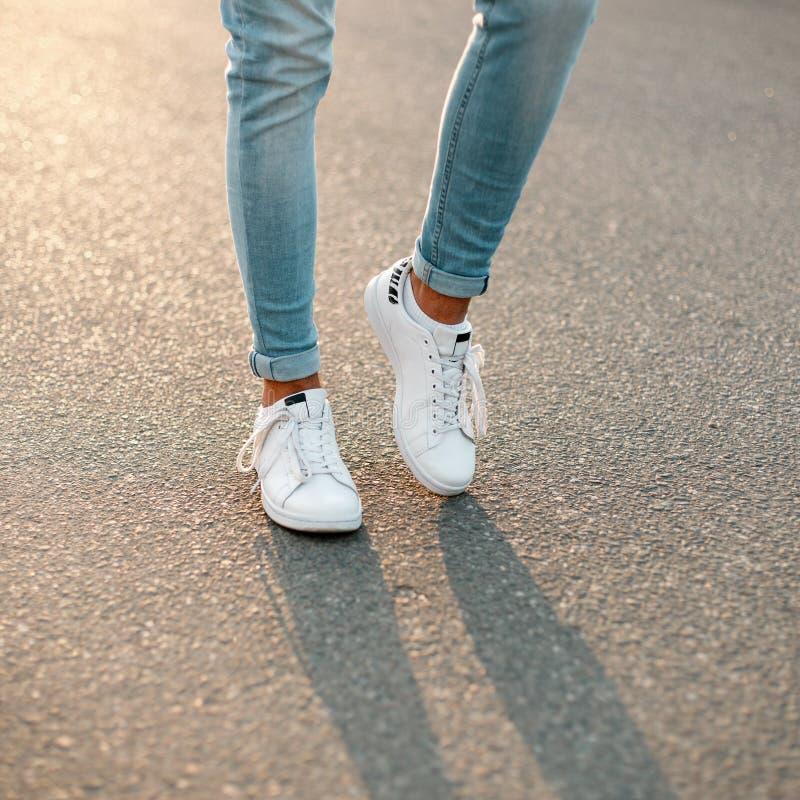 Le gambe degli uomini in jeans alla moda blu in scarpe da tennis alla moda bianche sui precedenti di asfalto Primo piano fotografie stock libere da diritti