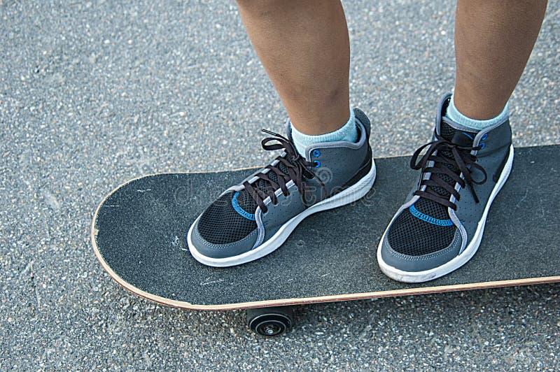 Le gambe dei bambini sullo skateboad sulla via immagini stock libere da diritti
