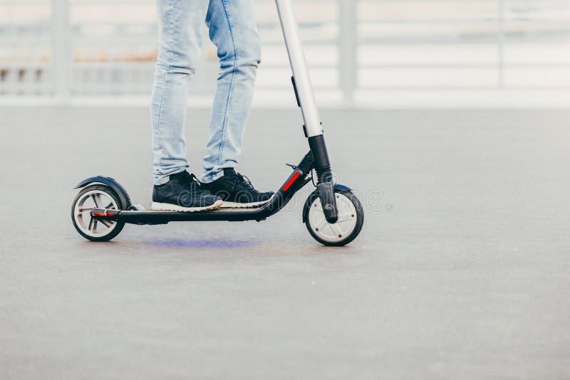 Le gambe del maschio sconosciuto nei giri neri dei jeans e delle scarpe da tennis sul motorino elettrico sopra asfalto urbano, go immagine stock