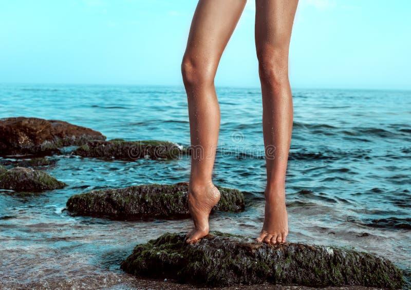 Le gambe della donna alla spiaggia immagini stock