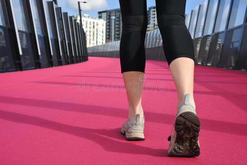 Le gambe della donna che camminano su una strada rosa luminosa fotografie stock libere da diritti
