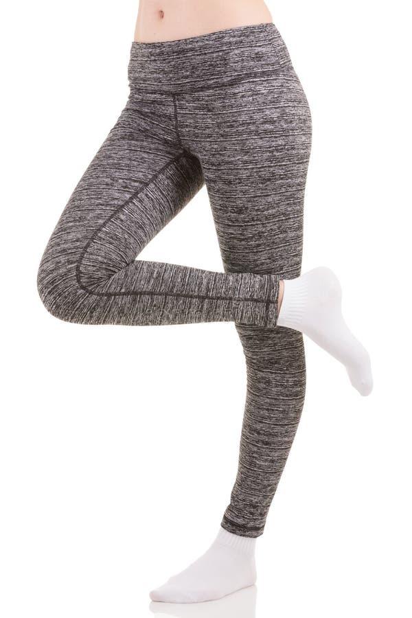 Le gambe della donna dal lato in pantaloni termici di sport grigi che stanno su una gamba con l'altra gamba si sono alzate in cal fotografia stock libera da diritti