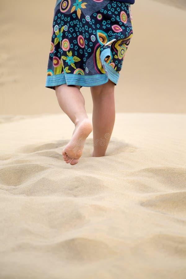 Le gambe della donna sulla sabbia fotografie stock
