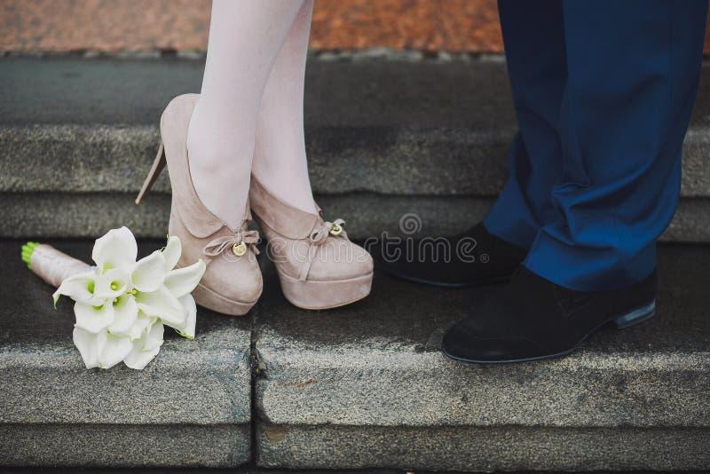 Le gambe della giovane coppia Donna ed uomo nell'amore Prima data datare proposta Baciare degli amanti Bei fiori della calla fotografie stock