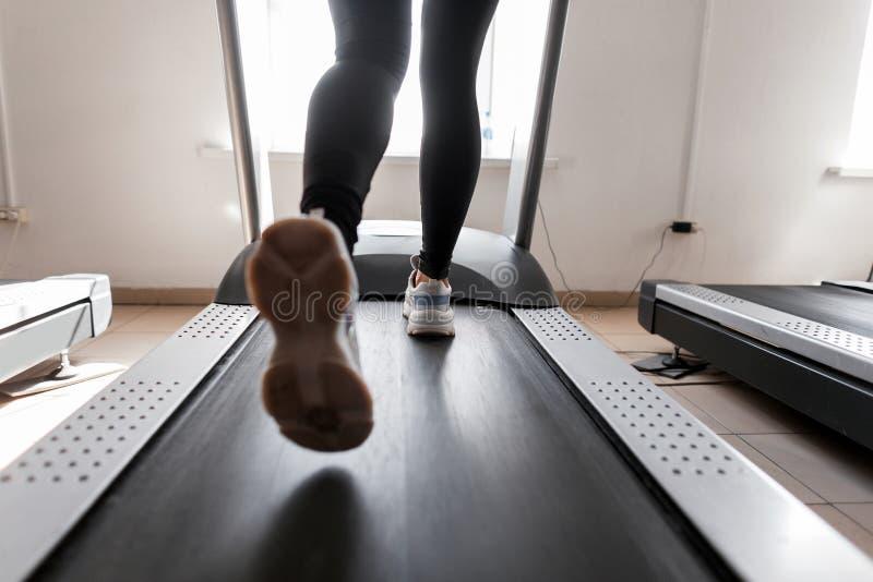 Le gambe delle donne funzionano su una pedana mobile Giovane donna impegnata nella forma fisica nella palestra Ragazza nell'addes immagine stock libera da diritti