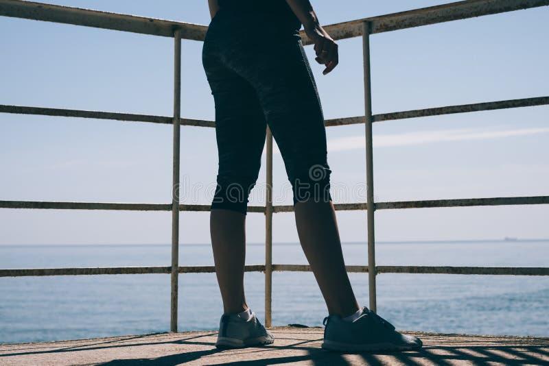 Le gambe delle donne snelle in scarpe da tennis blu e pantaloni atletici contro immagini stock