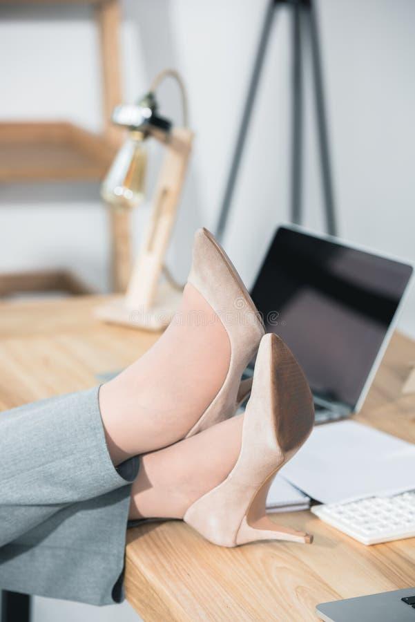 Le gambe delle donne in stiletti sulla tavola immagine stock